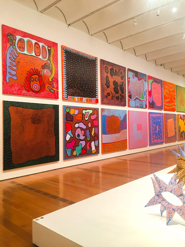 colorful square paintings on a tall gallery wall by kusama