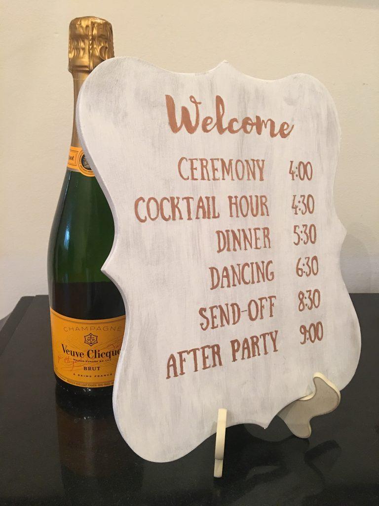 DIY wedding sign schedule next to champagne bottle