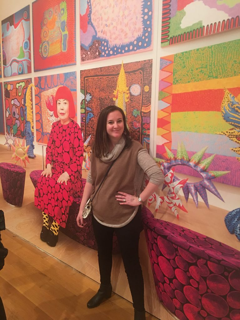 a picture of yayoi kusama and jen standing in front of it
