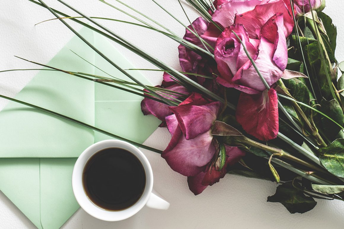 a bouquet of flowers, a cup of coffee, and a mint green envelope