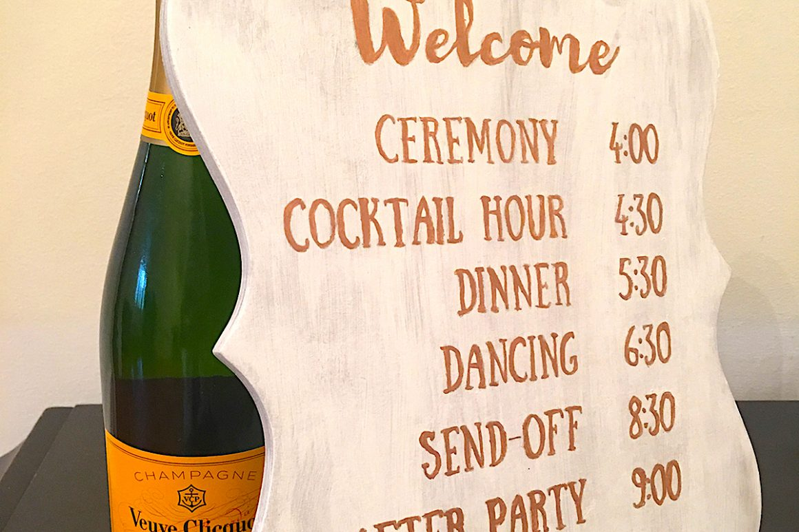 bottle of champagne next to wedding schedule sign