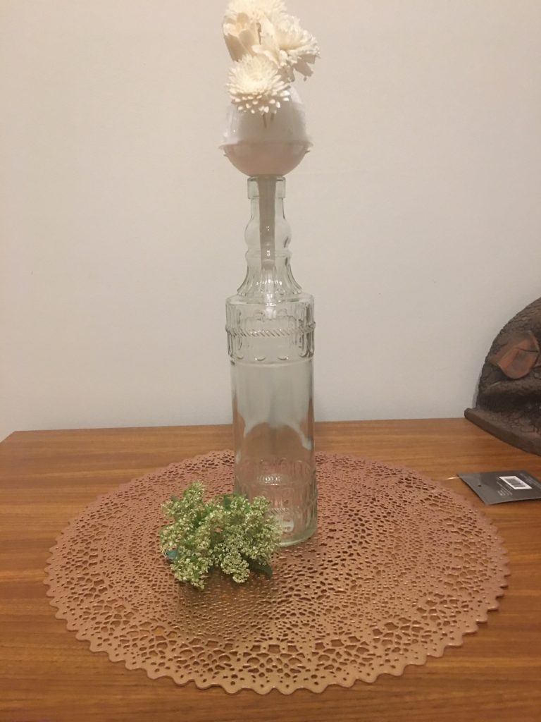 bottle with dried flowers and fake flowers in front of it