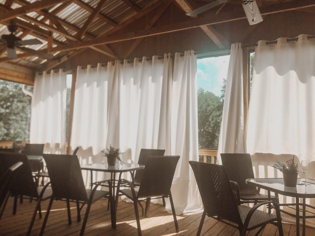 screened in patio with white curtains back patio cavender creek winery