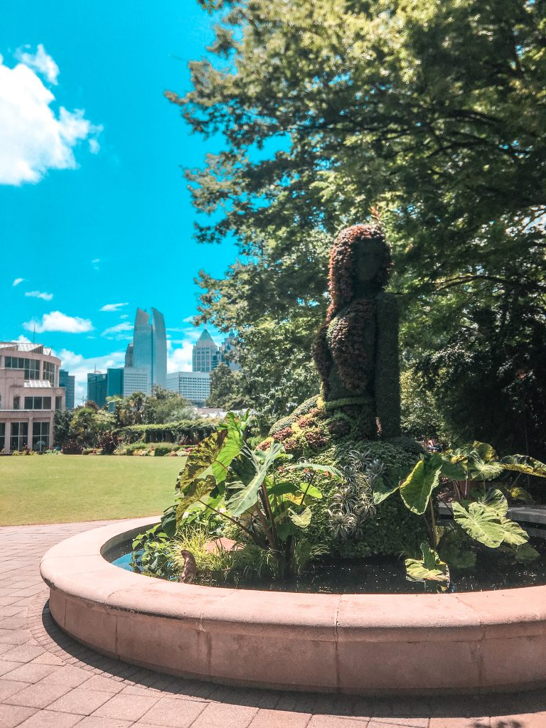 mermaid topiary at atlanta botanical garden with atlanta skyline in background