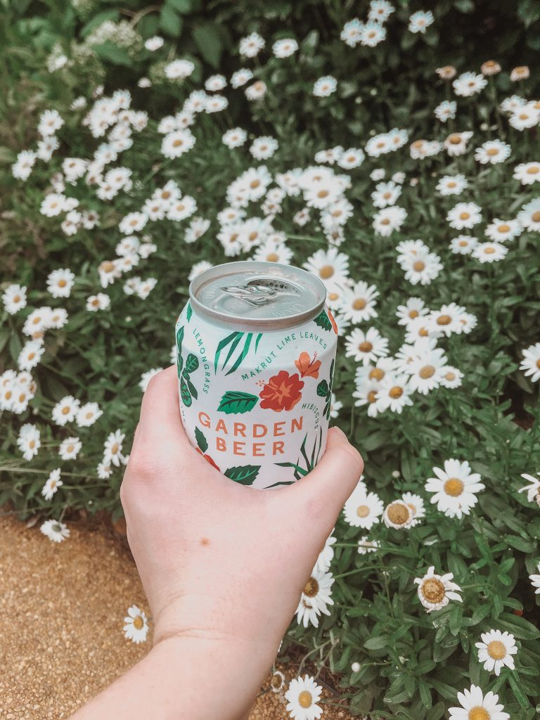 can of garden beer with white flowers in the background