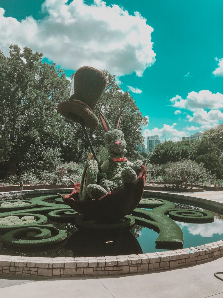 white rabbit topiary plant sculpture with atlanta skyline in background