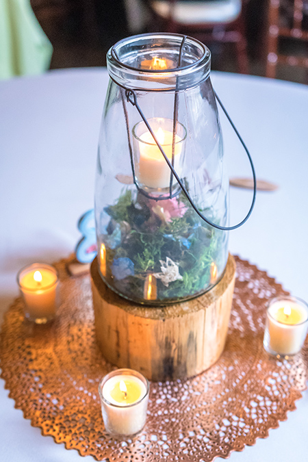 woodsy lantern wedding centerpiece with moss and candles