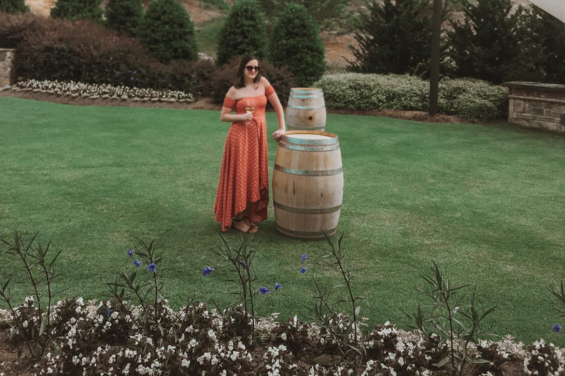 Standing next to a wine barrel at Yonah Mountain Vineyards