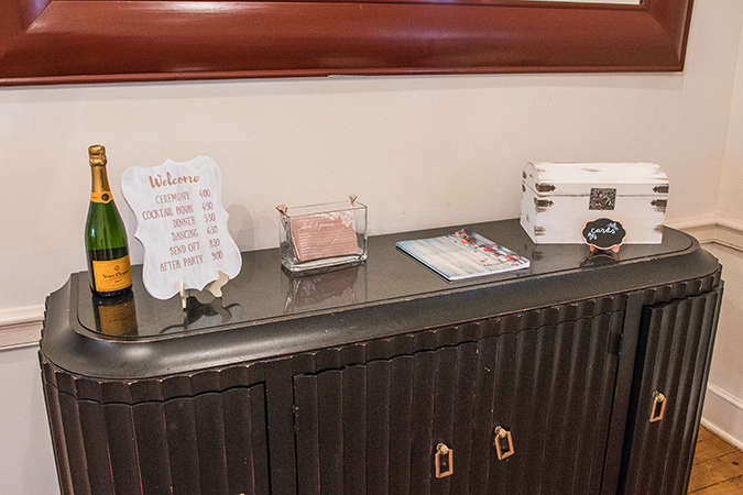 wedding welcome table with schedule, card box, and note cards.