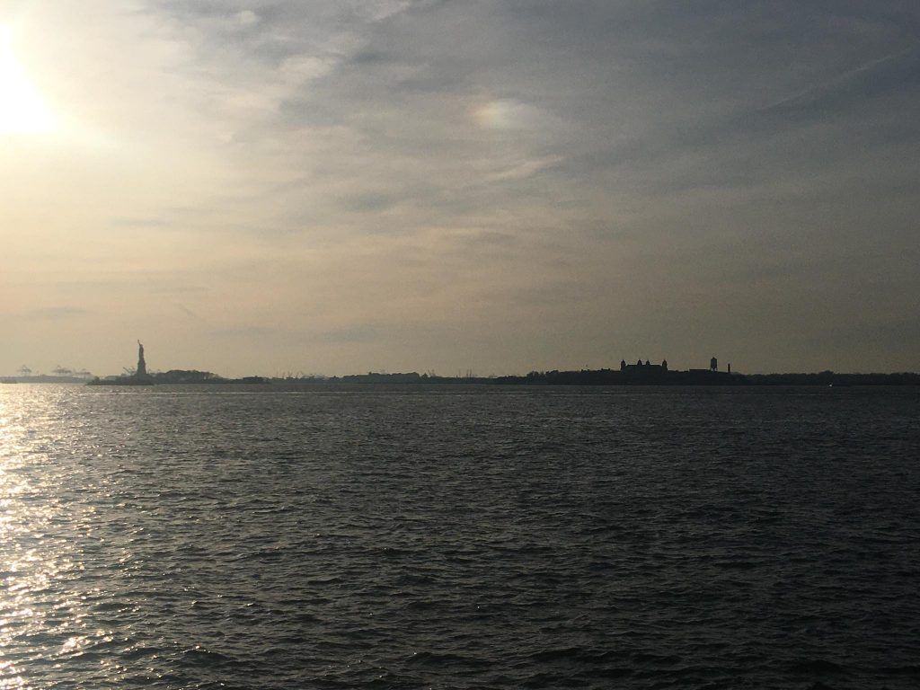 ellis island and statue of liberty silhouette at sunset