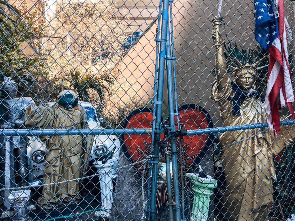 hodge podge of art and statues behind chain link fence