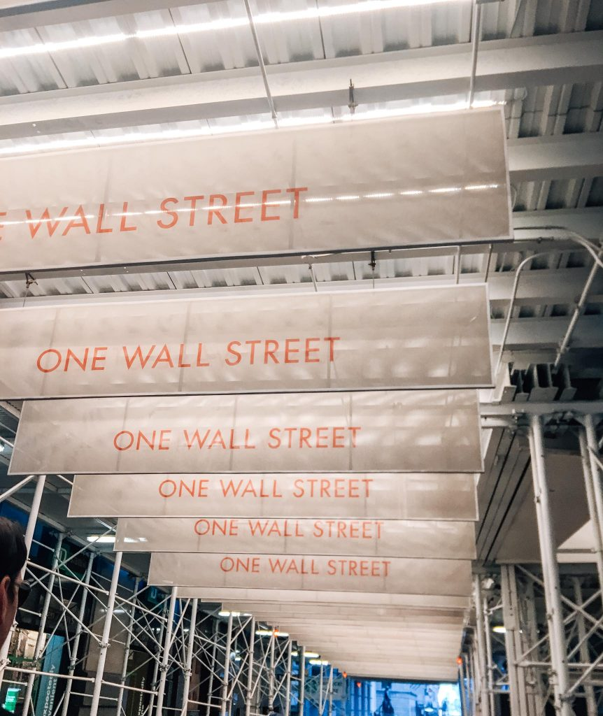 one wall street banners hang from scaffolding