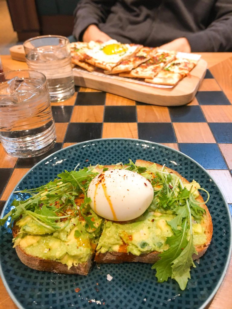 avocado toast with a soft boiled egg and a breakfast flatbread