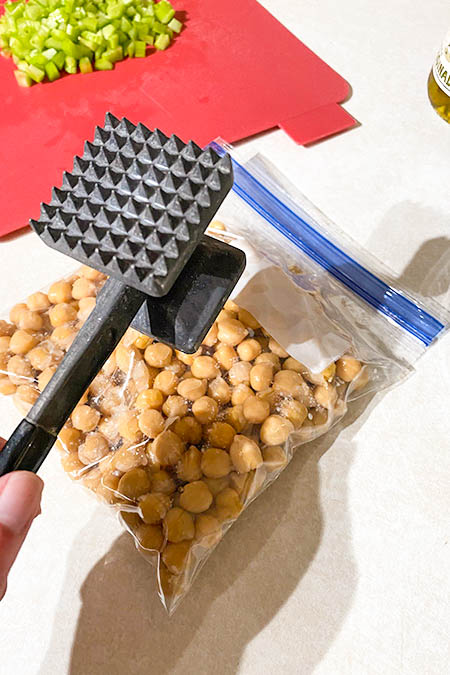 Put the chickpeas in a resealable bag and mash them with a meat tenderizer.